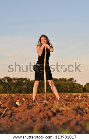 Beautiful girl with a shovel in a field in an evening dress - stock photo