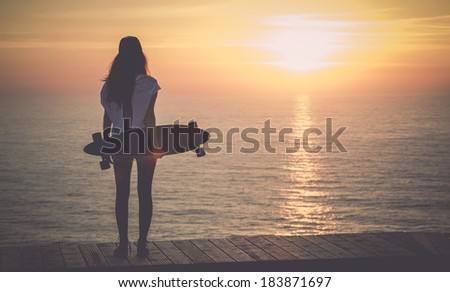 Beautiful girl with a skateboard looking to the sunset - stock photo
