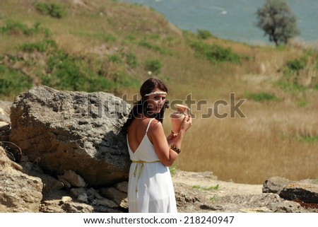 Beautiful girl with amphora in the image of an ancient goddess - stock photo