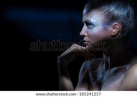 Beautiful girl with artistic make-up - stock photo