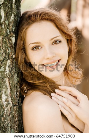 Beautiful girl with bared shoulders leans against tree in city park. - stock photo