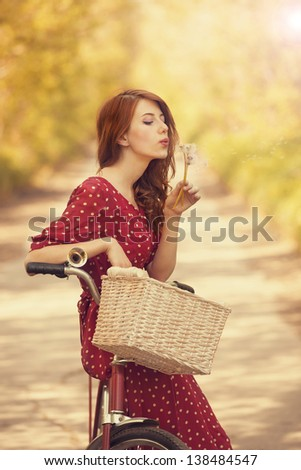 Beautiful girl with bike at countryside. Vintage. - stock photo