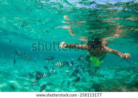 Beautiful girl with black hair has been snorkeling on the island of Mauritius in the Indian Ocean. She feeds the fish under water in clear turquoise water - stock photo