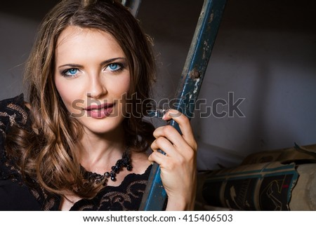 beautiful girl with blue eyes in a short black dress . with stairs storage - stock photo