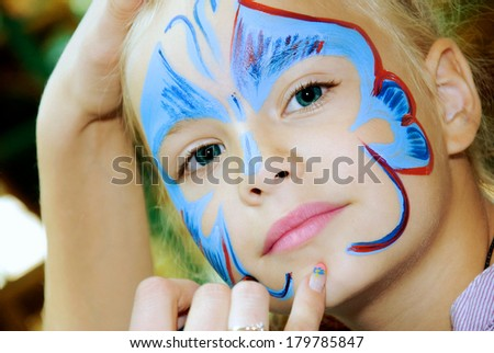 Beautiful girl with blue eyes with painted butterfly on her face - stock photo