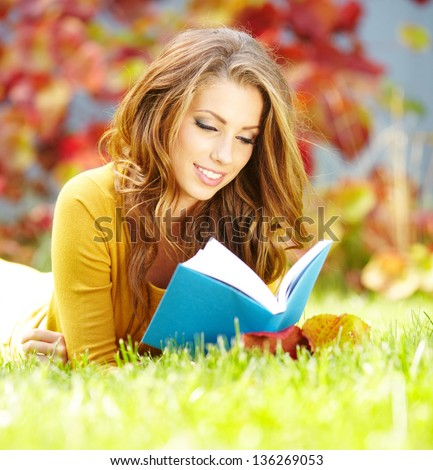 beautiful girl with book in  park - stock photo
