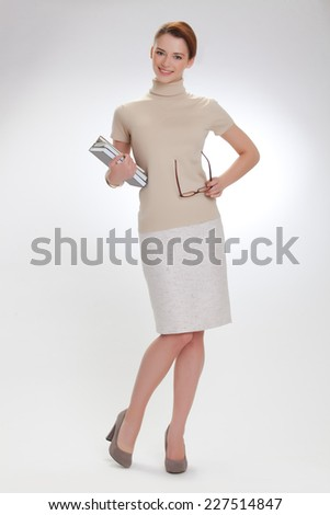 beautiful girl with books and wearing glasses in a beige jacket - stock photo