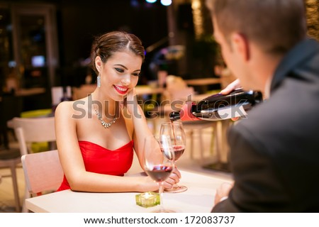 beautiful girl with  boyfriends in restaurant, he pouring wine in her glass - stock photo