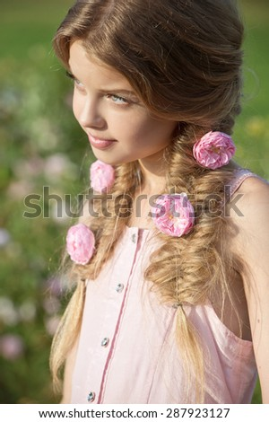 Beautiful girl with braids in garden of roses  - stock photo