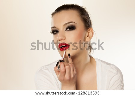 beautiful girl with bright makeup puts lip gloss - stock photo