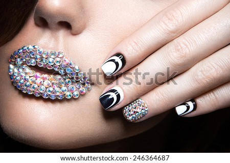Beautiful girl with bright nails and lips of crystals, long eyelashes and curls. Beauty face. Picture taken in a studio. - stock photo