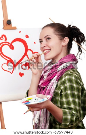 Beautiful girl with brushes near easel, painting on canvas. - stock photo
