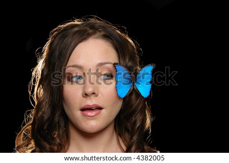 Beautiful girl with butterfly on her face against a black black ground - stock photo