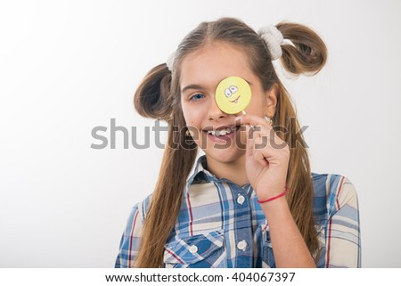 Beautiful girl with candy on a stick. Candy in the form of smiley. Girl and sweet. Cheerful teen girl eating candy on Stick, yellow smiley. Cute girl is looking at her colorful lollipop - stock photo