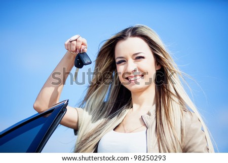 Beautiful girl with car key in hand - stock photo