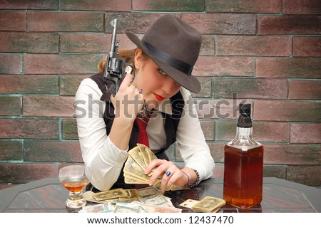 Beautiful girl with cards and gun over a wall - stock photo