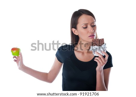 beautiful girl with chocolate and apple in hand on a white background - stock photo