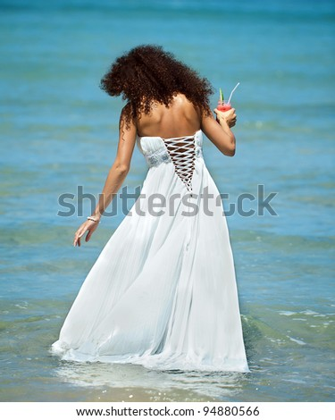 Beautiful girl with cocktail in hand comes in the ocean. Back view - stock photo