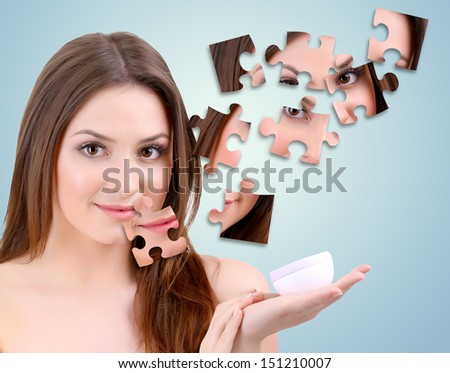Beautiful girl with cream with parts of skin on puzzles on blue background - stock photo