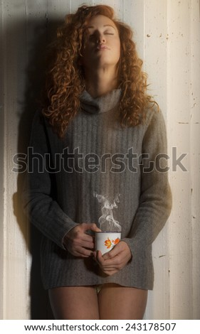 Beautiful girl with cup of coffee, hot chocolate or tea. Tinted image with special lighting effect. - stock photo