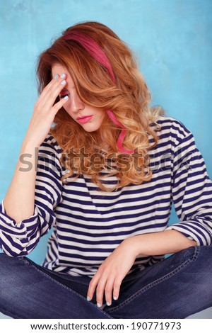 Beautiful girl with curly hair and a pink lock of hair dressed in a striped blouse posing on a blue background - stock photo