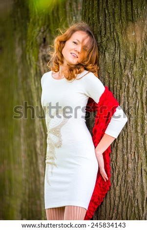 beautiful girl with curly hair on the background of a tree trunk - stock photo