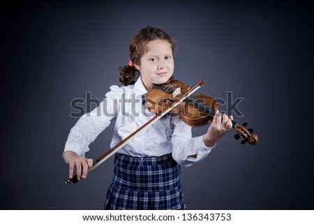 Beautiful girl with curly hair playing the old wooden violin on dark background - stock photo