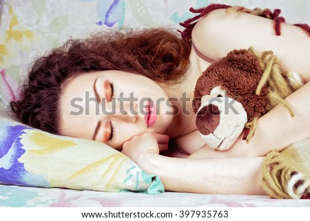 Beautiful girl with curly red hair sleeping in bed. Pretty young woman hugging a toy in sleep. Sweet dreams - stock photo