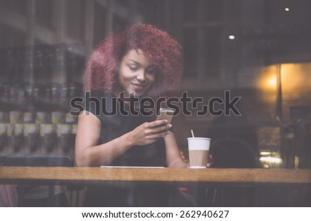 Beautiful girl with curly red hair typigin on smart phone in a cafe, seen through the window with buildings reflections - stock photo