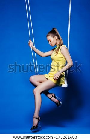 Beautiful girl with disco makeup posing on swing - stock photo