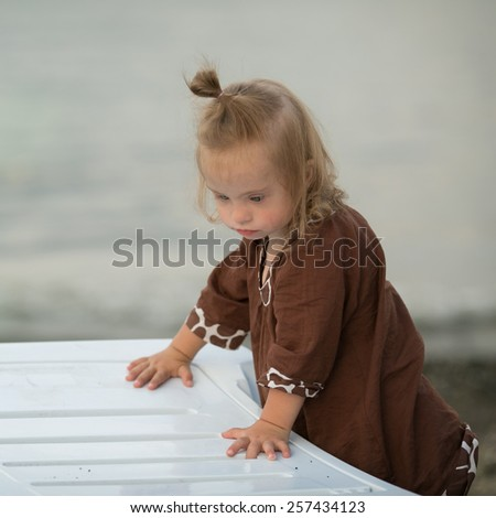 beautiful girl with Down syndrome on the beach - stock photo