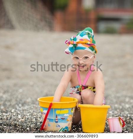 beautiful girl with Down syndrome playing with sand on the beach - stock photo