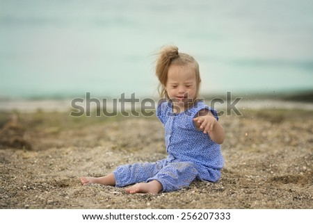 beautiful girl with Down syndrome throwing sand on the seashore - stock photo