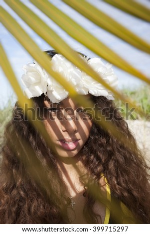 Beautiful girl with flower crown behind leaves - stock photo