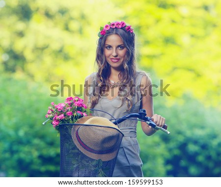 Beautiful girl with flowers in her hair and on her bicycle rides in a park - stock photo