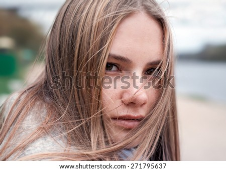 beautiful girl with freckles close-up, piercing look - stock photo