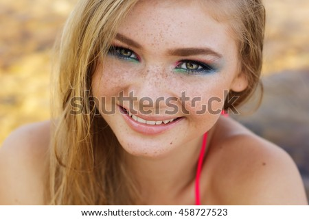 Beautiful girl with freckles over her face - stock photo