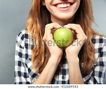 Beautiful girl with green apple on grey background - stock photo