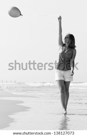 Beautiful girl with green balloon on the beach. Old style colors. - stock photo