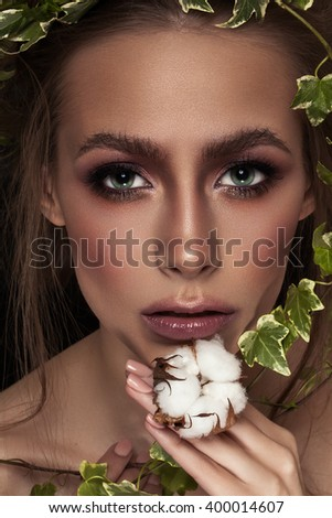 Beautiful Girl With Green Ivy. Beauty Model Woman Face. Perfect Skin. Professional Make-up. Makeup. Fashion Art - stock photo