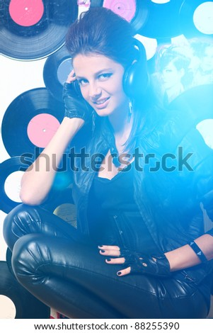 Beautiful girl with headphones in blue highlight against wall with vinyls - stock photo