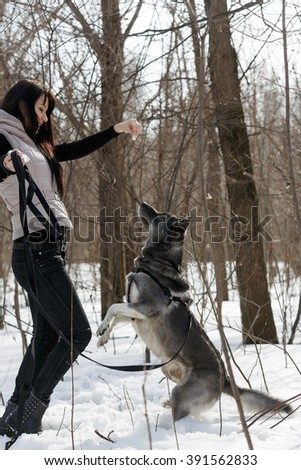 Beautiful girl with her dog in winter forest - stock photo