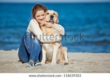 Beautiful girl with her dog  near sea - stock photo