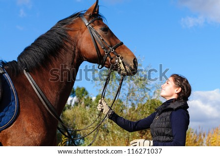 Beautiful girl with her horse. - stock photo