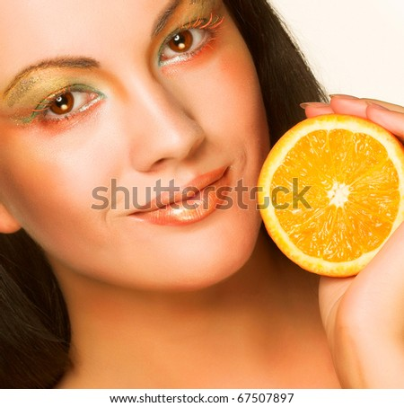 Beautiful girl with juicy orange - stock photo