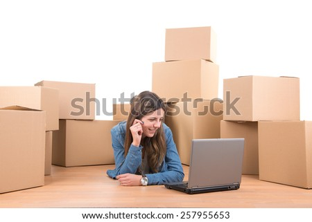 Beautiful girl with laptop and cardboard boxes unpacking in new home - stock photo