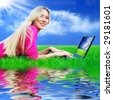 Beautiful girl with laptop on the blue sky and green grass background - stock photo