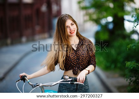 Beautiful girl with long fair hair is standing on the street on blouse and shorts with bicycle and smiling - stock photo