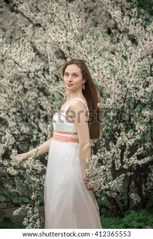 beautiful girl with long hair in a white dress walks in the lush garden - stock photo