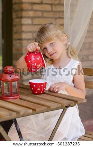 beautiful girl with long hair pouring tea into tea mug - stock photo
